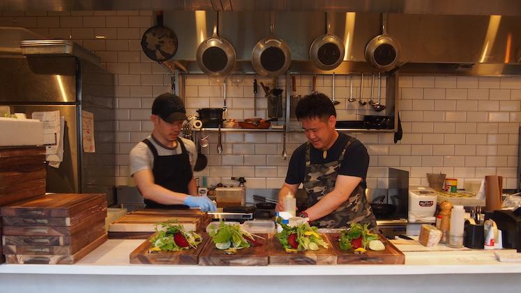 オープンキッチンで料理を作る酒井シェフ(右)。酒井シェフは、某老舗フルーツパーラーで果物のカットを学んだ「フルーツクチュリエ」でもある。